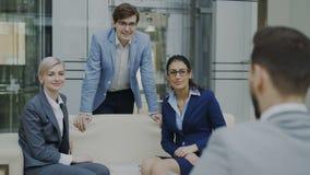 Team van vrolijke bedrijfscollega's die en elkaar spreken bespreken terwijl het hebben van onderbrekingszitting op bank in modern stock videobeelden
