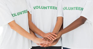 Team of volunteers putting hands together. On white background stock image