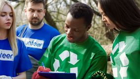 Team of volunteers during work. Close view of diverse cheerful volunteers preparing for cleanup of woods. The coordinator allocates responsibilities and royalty free stock image
