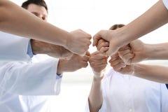 Team von Ärzten, die Hände auf hellen Hintergrund zusammenfügen Schattenbilder der Leute auf Hintergrund des blauen Himmels lizenzfreies stockbild