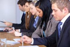 Team von 5 Leuten, die am Konferenztische sitzen Lizenzfreie Stockfotos