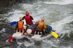Team von Athleten auf einem aufblasbaren Katamaran, das auf Wildwasser flößt lizenzfreie stockfotos