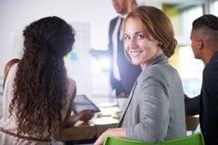 Team von den erfolgreichen Geschäftsleuten, die eine Sitzung im sonnenbeschienen vollziehendbüro haben lizenzfreie stockfotos
