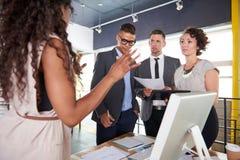 Team von den erfolgreichen Geschäftsleuten, die eine Sitzung im sonnenbeschienen vollziehendbüro haben Stockfotografie