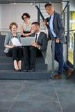 Team von den erfolgreichen Geschäftsleuten, die eine Sitzung im sonnenbeschienen vollziehendbüro haben Stockbilder