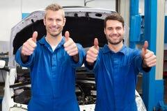Team von den Mechanikern, die an der Kamera lächeln Stockfoto
