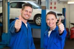 Team von den Mechanikern, die an der Kamera lächeln Lizenzfreies Stockfoto