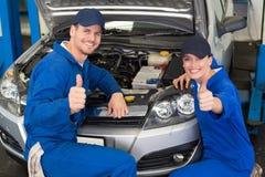 Team von den Mechanikern, die an der Kamera lächeln Lizenzfreies Stockbild