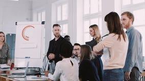 Team von den Unternehmenskollegen, die auf Frauenchef bei der modernen hellen Bürositzung hören Zeitlupe ROTES EPIC-W stock video