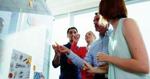 Team von den Unternehmensleitern, die über Glasbrett sich besprechen stock video footage