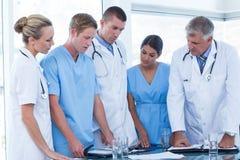 Team von Doktoren, die ihre Tagebücher betrachten Stockfotografie