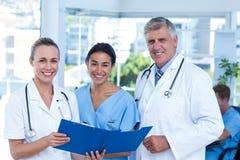 Team von Doktoren, die an ihren Dateien arbeiten und an der Kamera lächeln Stockfoto