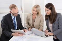 Team von drei Geschäftsleuten, die zusammen am Schreibtisch in einem Treffen sitzen Stockfotografie