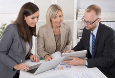 Team von drei Geschäftsleuten, die zusammen am Schreibtisch in einem Treffen sitzen Stockbilder