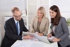 Team von drei Geschäftsleuten, die zusammen am Schreibtisch in einem Treffen sitzen Lizenzfreie Stockbilder