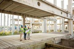 Team von erfolgreichen Architekten und von Teilhabern, die Arbeitsfortschritt auf einer Baustelle ?berpr?fen lizenzfreie stockfotografie