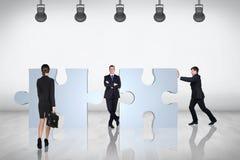 Team von Geschäftsleuten Versuch, zum sich des Puzzlespiels anzuschließen Stockfotografie