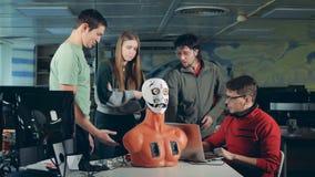 Team von Ingenieuren haben eine Diskussion über einem menschlich ähnlichen Roboter stock video