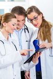 Team von jungen Doktoren in der Klinik mit Tablettencomputer Stockbild