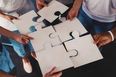 Team von jungen Geschäftsmännern kombinieren Stücke des Puzzlespiels Konzept der Integration und der Partnerschaft lizenzfreie stockfotografie