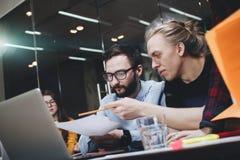 Team von jungen Technikstudenten arbeitet an einem neuen Projekt, stellt die Diskussion auf Papier und Laptop grafisch dar Stockfotos