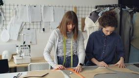 Team von kreativen Designern arbeitet mit Kleidungsmustern und -gewebe in Schneider ` s Shop Junge Frauen werden konzentriert stock video footage