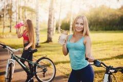 Team von Mädchen fahren mit Flasche Wasser im Park auf Sonnenunterganghintergrund rad lizenzfreie stockfotos
