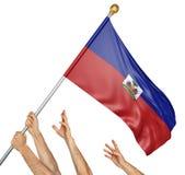 Team von Völkern übergibt das Hissen der Haiti-Staatsflagge Lizenzfreie Stockbilder