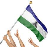 Team von Völkern übergibt das Hissen der Lesotho-Staatsflagge Stockfoto