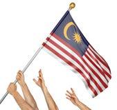 Team von Völkern übergibt das Hissen der Malaysia-Staatsflagge stockfotos