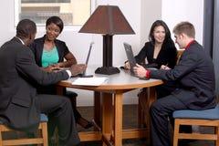 Team von vier arbeitend am Tisch Stockbild
