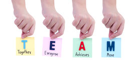 TEAM on woman hand 1. Woman hold word spell `TEAM` and handwriting together, everyone, achieve, more on notepaper in right hand with white / isolated background Stock Photography