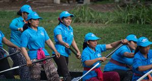 SIEM REAP, CAMBODIA - NOVEMBER, 2016: Team of women boat racers rest as they glide past the finish line. Team of women boat racers with blue jerseys rest as they Stock Photos