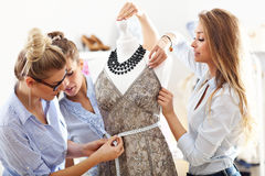 Team of women working on mannequin in atelier Stock Images