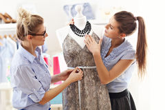 Team of women working on mannequin in atelier Stock Image