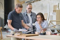 Team of woodworking workshop workers are discussing. Group of people client, designer or engineer and workers discuss work stock image