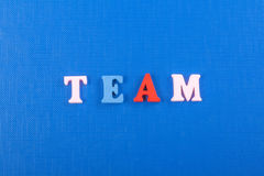 TEAM word on blue background composed from colorful abc alphabet block wooden letters, copy space for ad text. Learning Stock Photography