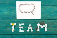 Team - word composed of the gears. And text box on the wooden desk royalty free stock photography