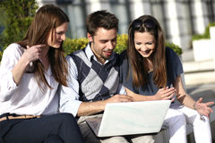Team work. Young group of people working on laptop outside and having fun Royalty Free Stock Photo