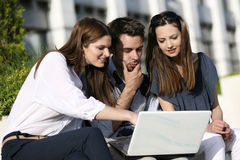 Team work. Young group of people working and discussing on laptop outside Royalty Free Stock Image