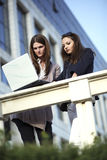 Team work. Two beautiful young females working on laptop outside Stock Image