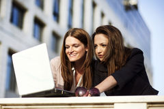 Team work. Two beautiful young females working on laptop outside Stock Photography