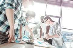 Positive delighted young people working in group. Team work. Cheerful partners standing around table and bowing heads while examining their project stock photos