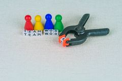 Team work concept - Figures in the line and an clamp tool as symbol for a working labor team collaboration.  Royalty Free Stock Photography