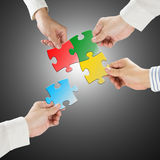 Team work concept, Hands hold puzzles connect each other with gr. Ay background Royalty Free Stock Image