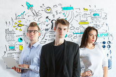 Team work concept. Young caucasian team on concrete background with business sketch. Team work concept royalty free stock images