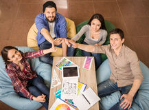 Team work. Creative group of designers putting hands together. Team work stock image