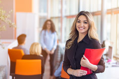 Team work discussing. Young woman with paper folder. Team work discussing. Open space office and startup crew brainstorming at new project. Young women with Royalty Free Stock Photos