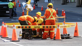 Team Work. A group of workers in orange clothes and yellow helmets replacing a pipe in a street in Toronto,Canada Royalty Free Stock Image