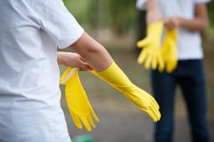 Two people, wearing latex glove for cleaning on hand on asphalt background. Rubbish on the back side. royalty free stock images